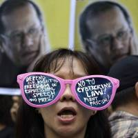 Photo -   A protester, wearing sunglasses with slogans, stands in front of picture of Philippine President Benigno Aquino III during a rally against the anti-cybercrime law in front of the Supreme Court in Manila, Philippines on Tuesday, Oct. 9, 2012. The Philippine Supreme Court on Tuesday suspended implementation of the country's anti-cybercrime law while it decides whether certain provisions violate civil liberties. (AP Photo/Aaron Favila)