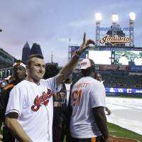 Photo - Cleveland Browns quarterback Johnny Manziel waves to fans before the Cleveland Indians play the Boston Red Sox in a baseball game, Wednesday, June 4, 2014, in Cleveland. (AP Photo/Tony Dejak)