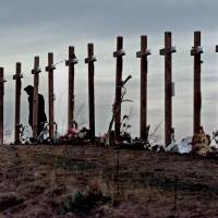 Photo - FILE - This April 28, 1999 file photo shows an unidentified woman with15 crosses posted on a hill above Columbine High School in Littleton, Colo. Wednesday, April 28, 1999 in remembrance of the 15 people who died during a school shooting on April 20. Sony Electronics and the Nielsen television research company collaborated on a survey ranking TV's most memorable moments. Other TV events include, the Sept. 11 attacks in 2001, Hurricane Katrina in 2005, the O.J. Simpson murder trial verdict in 1995 and the death of Osama bin Laden in 2011. (AP Photo/Eric Gay, file) ORG XMIT: NYET124