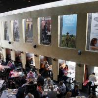 Photo - This Thursday, Feb. 21, 2013 photo shows people having lunch beneath Oscar posters at Kate Mantilini restaurant in Beverly Hills, Calif. The 85th Academy Awards are held on Sunday, Feb. 24, 2013, in Los Angeles. (AP Photo/Nick Ut)