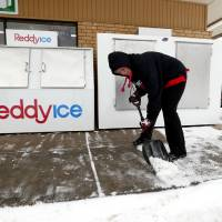Photo - 7-Eleven employee Kayla Kirlin shovels snow on Friday in Norman.  Photo by Steve Sisney, The Oklahoman  STEVE SISNEY - THE OKLAHOMAN