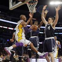 Photo - Los Angeles Lakers guard Kobe Bryant (24) passes as Oklahoma City Thunder center Hasheem Thabeet, center, and forward Nick Collison (4) defend in the first half of an NBA basketball game in Los Angeles, Sunday, Jan. 27, 2013. The Lakers won 105-96. (AP Photo/Reed Saxon) ORG XMIT: LAS104