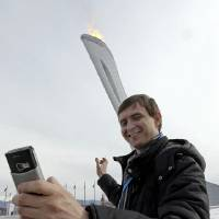 Photo - Sartakov Pavel Albertovich takes a selfie in front of the Olympic Cauldron at the 2014 Winter Olympics, Sunday, Feb. 9, 2014, in Sochi, Russia. (AP Photo/Morry Gash)
