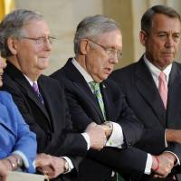 Photo - From left, House Minority Leader Nancy Pelosi of Calif., Senate Minority Leaders Mitch McConnell of Ky., Senate Majority Leader Harry Reid of Nev. and House Speaker John Boehner of Ohio hold hands as they sing,