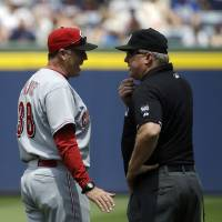 Photo - Umpire Bill Miller, right, talks with Cincinnati Reds manager Bryan Price after Miller ejected Price from the game for coming onto the field following an instant replay decision in favor of the Atlanta Braves in the first inning of a baseball game, Sunday, April 27, 2014, in Atlanta. (AP Photo/David Goldman)