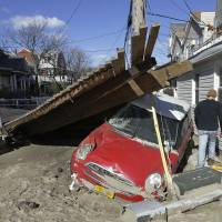 Photo - In this Nov. 3, photo, a man passes walks by a piece of the Rockaways boardwalk that was washed into Beach 91st Street, alongside a small car that was destroyed by Superstorm Sandy earlier in the week, in the Rockaways neighborhood in New York. AP Photo  Kathy Willens - AP