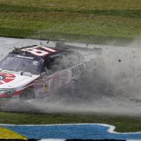 Photo - Driver Joe Nemechek slides through the grass after losing control of his car during the NASCAR Nationwide Series auto race Saturday, Feb. 23, 2013, at Daytona International Speedway in Daytona Beach, Fla. (AP Photo/Chris O'Meara)
