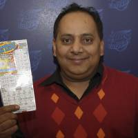 Photo - FILE - This undated file photo provided by the Illinois Lottery shows Urooj Khan, 46, of Chicago's West Rogers Park neighborhood, posing with a winning instant lottery ticket. On Friday, Jan 11, 2013, a Cook County judge granted authorities permission to exhume the body of the Chicago lottery winner who was fatally poisoned with cyanide just as he was about to collect his $425,000 payout. His July 20 death was initially ruled a result of natural causes. (AP Photo/Illinois Lottery, File)