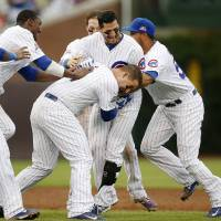 Photo - Chicago Cubs players pile onto Justin Ruggiano, center, after Ruggiano hit a game winning RBI single against the Atlanta Braves during the ninth inning of a baseball game on Friday, July 11, 2014, in Chicago. The Chicago Cubs won 5-4. (AP Photo/Andrew A. Nelles)