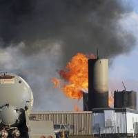 Photo - In this Monday, July 7, 2014 file photo, a saltwater disposal facility burns after it was struck by lightning, near Alexander, N.D.  Three massive fires since the beginning of June have highlighted the threat lightning poses in the North Dakota oil patch, and in each case it was tanks that store the toxic saltwater associated with drilling, not the oil wells or drilling rigs, that were to blame.  (AP Photo/Josh Wood, File)