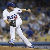 Photo - Los Angeles Dodgers starting pitcher Clayton Kershaw follows through on a pitch in the third inning of Game 4 in the National League baseball division series against the Atlanta Braves, Monday, Oct. 7, 2013, in Los Angeles. (AP Photo/Danny Moloshok)