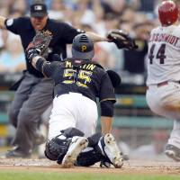 Photo - Pittsburgh Pirates catcher Russell Martin (55) shows his glove to home plate umpire Doug Eddings as he calls Arizona Diamondbacks' Paul Goldschmidt (44) safe when he scored from second on a hit by Miguel Montero in the fifth inning of the baseball game on Tuesday, July 1, 2014, in Pittsburgh. (AP Photo/Keith Srakocic)