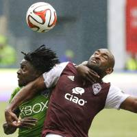 Photo - Seattle Sounders' Obafemi Martins, left, and Colorado Rapids' Marvell Wynne battle for a header in the second half of an MLS soccer match, Saturday, Aug. 30, 2014, in Seattle. The Sounders defeated the Rapids 1-0. (AP Photo/Ted S. Warren)