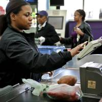 Photo - Employee Jasmine Blackwell works Wednesday the register at the grocery store at NE 23 and Martin Luther King Avenue in Oklahoma City .  Photo by Chris Landsberger, The Oklahoman  CHRIS LANDSBERGER - CHRIS LANDSBERGER