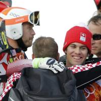 Photo - Men's supercombined gold medalist, Switzerland's Sandro Viletta, right, embraces another athlete as United States' Bode Miller, left, stands nearby in the finish area of the Alpine ski venue at the Sochi 2014 Winter Olympics, Friday, Feb. 14, 2014, in Krasnaya Polyana, Russia. (AP Photo/Christophe Ena)