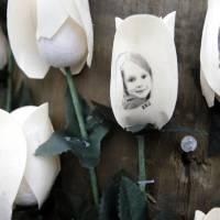 Photo - Photos showing those killed in the shootings at Sandy Hook Elementary School are imprinted on fake roses at a memorial in the Sandy Hook village of Newtown, Conn., Saturday, Dec. 22, 2012. (AP Photo/Seth Wenig)