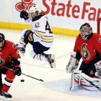 Photo - Buffalo Sabres' Nathan Gerbe (42) jumps as he screens a shot on Ottawa Senators goaltender Craig Anderson (41) as Mike Lundin (10) watches during the first period of their NHL hockey game, Tuesday, Feb. 12, 2013, in Ottawa, Ontario. (AP Photo/The Canadian Press, Fred Chartrand)