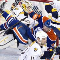 Photo - Nashville Predators goalie Carter Hutton (30) is crashed into by Edmonton Oilers Taylor Hall (4) during second period NHL hockey action in Edmonton, Canada, Sunday, Jan. 26, 2014. (AP Photo/The Canadian Press, Jason Franson)