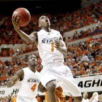Photo - OSU's Terrel Harris moves to the basket in front of Anthony Brown during the NCAA college basketball game between Oklahoma State University and Texas in Stillwater, Okla., Saturday, Feb. 28, 2009. PHOTO BY BRYAN TERRY, THE OKLAHOMAN ORG XMIT: KOD