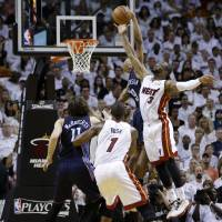 Photo - Miami Heat's Dwyane Wade (3) shoots over Charlotte Bobcats' Gerald Henderson, second from right, during the second half in Game 1 of an opening-round NBA basketball playoff series on Sunday, April 20, 2014, in Miami. The Heat defeated the Bobcats 99-88. (AP Photo/Lynne Sladky)