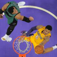 Photo - Los Angeles Lakers guard Kent Bazemore, right, goes up for a shot as Boston Celtics center Jared Sullinger defends during the first half of an NBA basketball game, Friday, Feb. 21, 2014, in Los Angeles. (AP Photo/Mark J. Terrill)