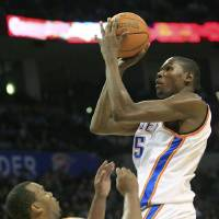 Photo - Oklahoma City Thunder forward Kevin Durant, right, fouls Houston Rockets center Chuck Hayes, left, as he goes up for a shot in the third quarter of an NBA basketball game in Oklahoma City, Sunday, Nov. 29, 2009. Durant had 25 points for Oklahoma City, but Houston won 100-91. (AP Photo/Sue Ogrocki) ORG XMIT: OKSO106