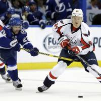 Photo - Washington Capitals center Mikhail Grabovski (84), of Germany, avoids a hook by Tampa Bay Lightning right wing Martin St. Louis (26) during the second period of an NHL hockey game Thursday, Jan. 9, 2014, in Tampa, Fla. (AP Photo/Chris O'Meara)