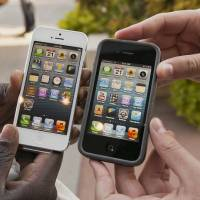 Photo - Noah Meloccaro, right, compares his older iPhone 4s to the new iPhone 5 held by Both Gatwech on Sept. 21 outside an Apple Store in Omaha, Neb. AP Photo  Nati Harnik