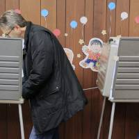 Photo -   A man and woman vote at Hyde Park Public Library, Tuesday, Nov. 6, 2012, in Cincinnati. After a grinding presidential campaign, Americans head into polling places across the country.(AP Photo/Al Behrman)