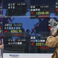 Photo - A TV crew reports stock princes in front of an electronic stock indicator of a securities firm in Tokyo, Monday, March 25, 2013. A last-minute package of rescue loans that saves Cyprus from a banking collapse and bankruptcy helped push Asian stock markets higher Monday. Japan's Nikkei 225 index surged 1.9 percent to 12,546.46. (AP Photo/Shizuo Kambayashi)