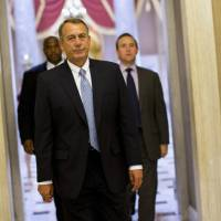 Photo - House Speaker John Boehner of Ohio walks to his office on Capitol Hill in Washington, Wednesday, Oct. 2, 2013. The Republican-run House has rejected an effort by Democrats to force a quick end to the partial government shutdown. By a 227-197 vote Wednesday, the House rejected a move by Democrats aimed at forcing the House to vote on immediately reopening the government without clamping any restrictions on President Barack Obama's health care law. (AP Photo/ Evan Vucci)