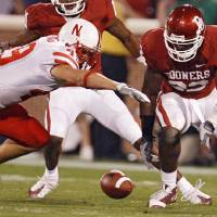 Photo - Oklahoma's Keenan  Clayton (22) goes after a fumble he forced on Nebraska's Dreu Young (49) during the first half of the college football game between the University of Oklahoma Sooners (OU) and the University of Nebraska Huskers (NU) at the Gaylord Family-Oklahoma Memorial Stadium, on Saturday, Nov. 1, 2008, in Norman, Okla. BY NATE BILLINGS, THE OKLAHOMAN