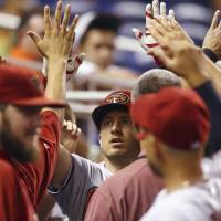 Photo - Arizona Diamondbacks' Cliff Pennington celebrates in the dugout after hitting a home run during the first inning of a baseball game in Miami against the Miami Marlins, Friday, Aug. 15, 2014.  (AP Photo/J Pat Carter)