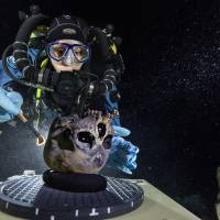 Photo - In this June 2013 photo provided by National Geographic, diver Susan Bird, working at the bottom of Hoyo Negro, a large dome-shaped underwater cave in Mexico's Yucatan Peninsula, brushes a human skull found at the site while her team members take detailed photographs. Thousands of years ago, a teenage girl fell into this deep hole and died. Now, her skeleton and her DNA are helping scientists study the origins of the first Americans. An analysis of her remains was released Thursday, May 15, 2014 by the journal Science. Her DNA links her to an ancient land bridge connecting Asia and North America, and suggests she shares ancestors with the modern native peoples of the Americas. (AP Photo/National Geographic, Paul Nicklen)