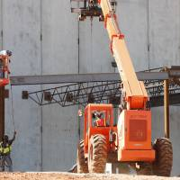 Photo - Workers lift the last piece of structural steel for the Deer Creek Performing Arts and Athletic Center.