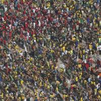 Photo - Soccer fans gather before a live broadcast of the World Cup round of 16 match between Brazil and Chile, inside the FIFA Fan Fest area on Copacabana beach, in Rio de Janeiro, Brazil, Saturday, June 28, 2014. (AP Photo/Silvia Izquierdo)