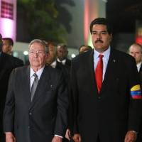 Photo - In this photo released by Miraflores Press Office, Cuba's President Raul Castro, left,  and Venezuela's Vice President Nicolas Maduro stand upon their arrival to the Fort Tiuna military academy to visit the coffin containing the body of Venezuela's late President Hugo Chavez during his wake in Caracas, Venezuela, Thursday, March 7, 2013. Maduro, Venezuela's acting president, said Chavez's  remains will be put on permanent display at the Museum of the Revolution, close to the presidential palace where Chavez ruled for 14 years. A state funeral for Chavez attended by some 33 heads of government is scheduled to begin Friday morning. (AP Photo/Miraflores Press Office)