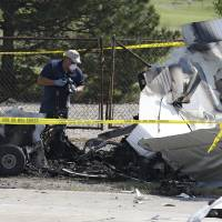 Photo - Investigators look over the wreckage of a plane that crashed as it rests on the side of a road Tuesday, Aug. 26, 2014, in Richmond Heights, Ohio. The Cessna 172R crashed and burst into flames just after takeoff from a regional airport outside of Cleveland on Monday, killing all four people on board, according to the Ohio State Highway Patrol. (AP Photo/Tony Dejak)