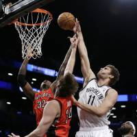 Photo - Brooklyn Nets center Brook Lopez (11) shoots over the defense of Toronto Raptors forward Ed Davis (32) and center Aaron Gray (34) in the first half of an NBA basketball game Tuesday, Jan. 15, 2013, in New York. (AP Photo/Kathy Willens)
