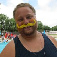 Photo - Eddie Hudson sports a mock yellow mustache as a member of the yellow team during Camp Chaverim's recent Maccabiah Games theme day. Hudson is in charge of youths in the camp's leaders-in-training program.