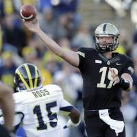 Photo -   Purdue quarterback Caleb TerBush (19) throws over Michigan linebacker James Ross III during the first half of an NCAA college football game in West Lafayette, Ind., Saturday, Oct. 6, 2012. (AP Photo/Michael Conroy)