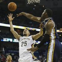 Photo - New Orleans Pelicans guard Austin Rivers (25) shoots around Utah Jazz center Derrick Favors (15) in the first half of an NBA basketball game in New Orleans, Friday, March 28, 2014. (AP Photo/Bill Haber)