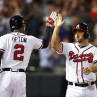 Photo - Atlanta Braves second baseman Dan Uggla, right,  celebrates with teammate B.J. Upton, left, after scoring on a Ryan Doumit base hit in the seventh inning of a baseball game  against Milwaukee Brewers Thursday, May 22, 2014 in Atlanta. (AP Photo/John Bazemore)
