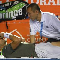 Photo - Spain's David Ferrer is treated after injuring his right leg while playing South Africa's Kevin Anderson at the Mexican Tennis Open in Acapulco, Mexico, Thursday, Feb. 27, 2014. Ferrer retired from the match and Anderson won the match. (AP Photo/Hugo Avila, JAM MEDIA)