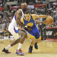 Photo -   Los Angeles Clippers forward Lamar Odom, left, defends as Golden State Warriors guard Stephen Curry (30) drives to the basket in the first half of an NBA basketball game in Los Angeles on Saturday, Nov. 3, 2012. (AP Photo/Richard Hartog) ,