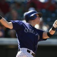 Photo - Colorado Rockies' Corey Dickerson watches his solo home run against the San Francisco Giants in the fifth inning of the Rockies' 9-2 victory in a baseball game in Denver on Wednesday, Sept. 3, 2014. (AP Photo/David Zalubowski)