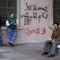 Photo - Egyptian men stand near Arabic writing on a wall in Arabic that reads,