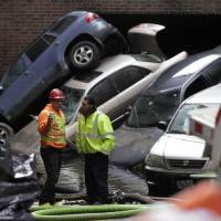 Photo -   FILE- In this Friday, Nov. 2, 2012, file photo, cars that were uprighted and submerged by Superstorm Sandy remain at the entrance of a subterranean parking garage in New York's Financial District, as the water is pumped out. Thanksgiving travelers who have yet to rent a car in the Northeast are out of luck: Superstorm Sandy has created a shortage. The storm damaged thousands of cars, including those owned by the rental companies. The loss of vehicles was compounded by rising demand. Thanksgiving and Christmas are normally busy rental periods. And lingering mass transit problems caused by Sandy have added to demand. (AP Photo/Richard Drew, File)