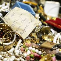 Photo - This Jan. 2, 2013 photo shows a pile of primarily costume jewelry among the mass of seized stolen goods during a news conference at Hudson Falls Village Court in Hudson Falls, N.Y. Few clues exist pointing to the owners of the roughly 30,000 items discovered after 39-year-old burglary suspect John Suddard's recent arrest. So police are taking the novel step of displaying the items at the local high school Wednesday night, Jan. 9, 2013. (AP Photo/The Post-Star, Derek Pruitt)