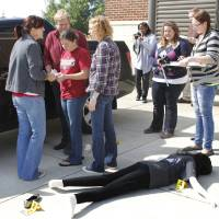 Photo - University of Central Oklahoma students discuss evidence during a crime scene processing class. In a cordoned-off area, numerical markers were placed beside a facedown victim — a mannequin — and other evidence.